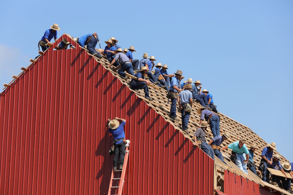 A group of hard working men in the process of completing the roof of red a steel horse barn for a ranch owner