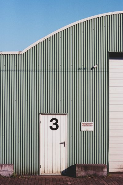 A newly built light green steel warehouse with a white roof for a manufacturing company