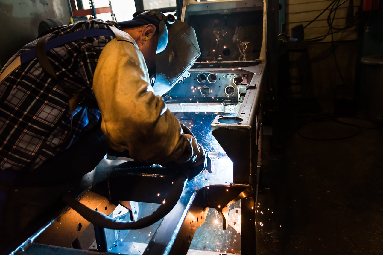 A man welding a new project in his freshly assembled steel workshop